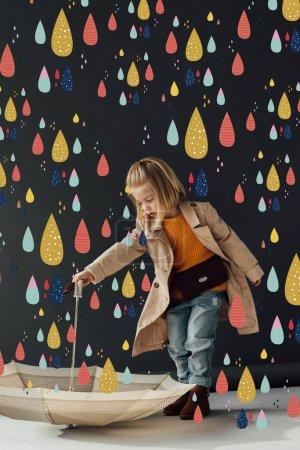 Photo pour Enfant sérieux en trench coat et jeans tenant parapluie sous la pluie colorée fée - image libre de droit
