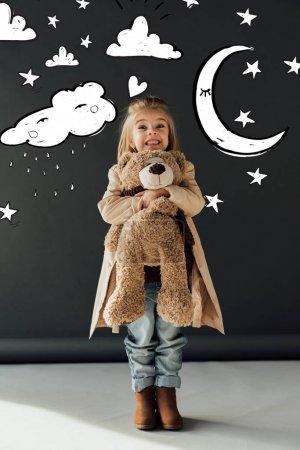 Photo pour Enfant heureux et mignon dans le trench-coat et les jeans étreignant l'ours de nounours sur le fond noir avec la lune magique, les étoiles et l'illustration pluvieuse de nuage - image libre de droit