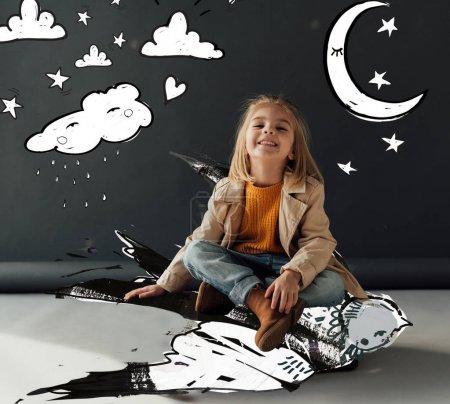 Photo pour Enfant souriant et mignon se reposant avec des jambes croisées volant sur l'oiseau de fantaisie sur le fond noir avec la lune magique, les étoiles et l'illustration pluvieuse de nuage - image libre de droit