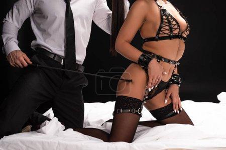 Photo pour Vue recadrée de bdsm couple avec pile sur lit sur noir - image libre de droit