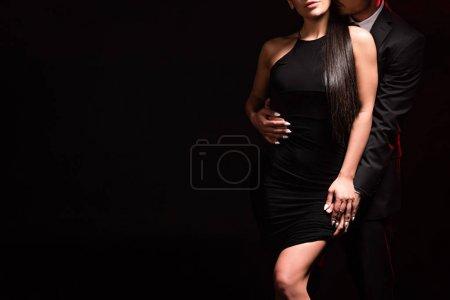 Photo pour Vue recadrée de couple élégant embrassant sur le noir - image libre de droit