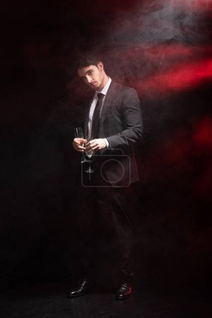 Photo for Full length view of handsome man in formal wear holding wineglasses in smoke on black - Royalty Free Image