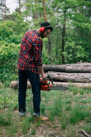 Photo pour Homme barbu adulte en chemise à carreaux et cache-oreilles tenant une tronçonneuse dans la forêt - image libre de droit