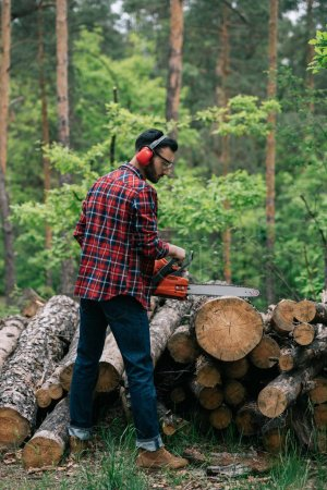 bearded lumberer in hearing protectors cutting trunk with chainsaw in forest