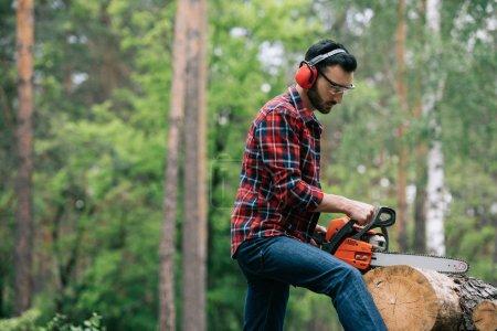 Photo pour Bûcheron attentif dans les protecteurs d'audition coupant le tronc avec la tronçonneuse dans la forêt - image libre de droit