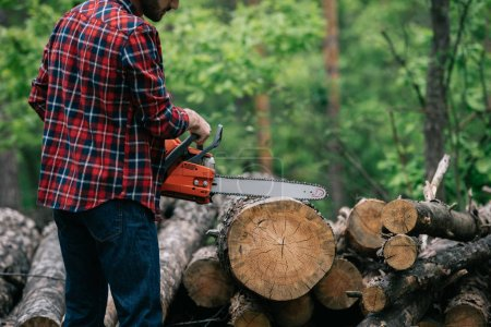 Photo for Partial view of lumberjack cutting trunk with chainsaw in forest - Royalty Free Image
