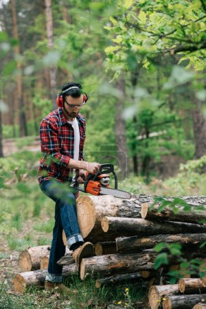Photo for Lumberman in earmuffs and protective glasses cutting trunks with chainsaw in forest - Royalty Free Image