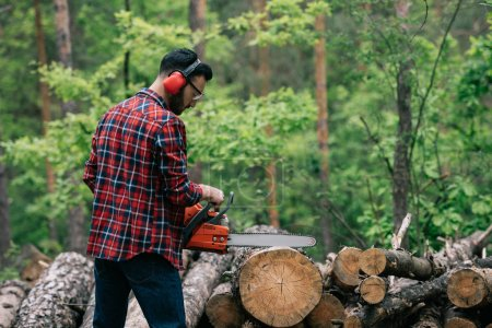 Photo for Bearded lumberer in plaid shirt cutting trunks with chainsaw in wood - Royalty Free Image