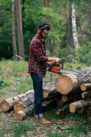 Foto de Leñador barbudo en auriculares con cancelación de ruido cortando madera con motosierra en el bosque - Imagen libre de derechos