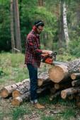 """Постер, картина, фотообои """"бородатый лесоруб в шумоподавляющих наушниках рубит дрова бензопилой в лесу"""""""