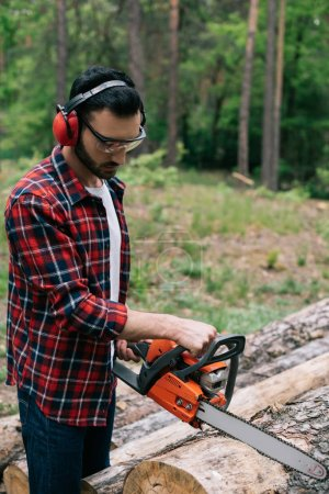 attentive lumberer in checkered shirt cutting wood with chainsaw in forest
