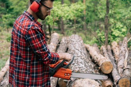 Photo for Concentrated lumberer in earmuffs and protective glasses cutting wood with chainsaw in forest - Royalty Free Image