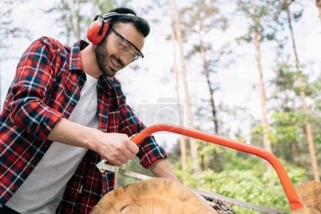 Photo pour Bûcheron souriant dans des cache-oreilles et des verres protecteurs coupant le journal avec la main dans la forêt - image libre de droit