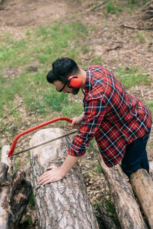 Photo for Lumberjack in checkered shirt and noise-canceling headphones cutting log with handsaw in forest - Royalty Free Image