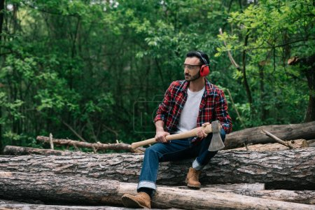 Photo for Pensive lumberman with ax sitting on logs in forest and looking away - Royalty Free Image