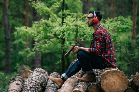 Photo pour Bûcheron réfléchi tenant la hache tout en s'asseyant sur des rondins dans la forêt et regardant loin - image libre de droit
