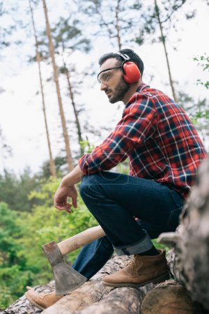 Photo pour Bûcheron pensif tenant la hache et regardant loin tout en s'asseyant sur des rondins dans la forêt - image libre de droit