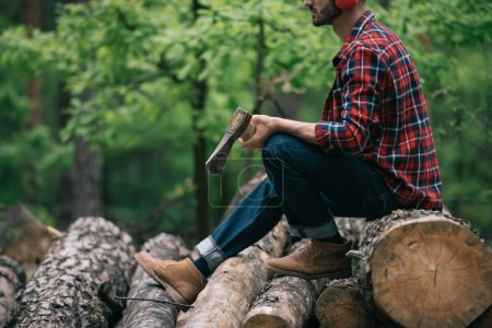 Photo for Cropped view of lumberjack holding ax while sitting on tree trunks in forest - Royalty Free Image