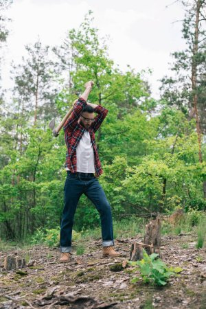 Photo for Lumberman in checkered shirt and denim jeans cutting wood with ax in forest - Royalty Free Image