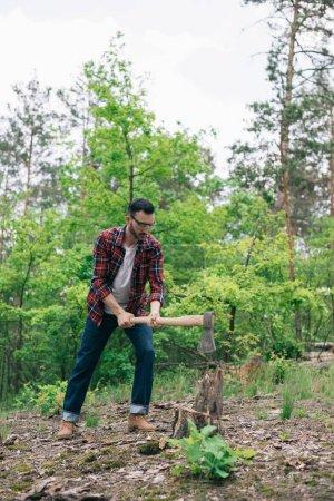 Photo pour Bûcheron en chemise à carreaux et jeans en denim coupant le bois avec hache en forêt - image libre de droit