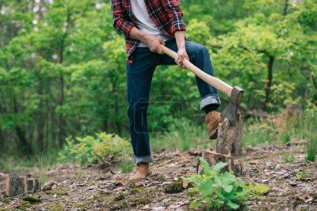 Foto de Vista parcial del leñador en camisa a cuadros y jeans demezcles cortando madera con hacha en el bosque - Imagen libre de derechos