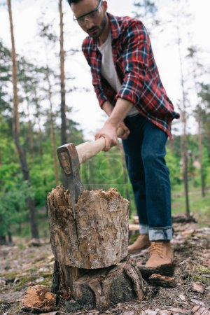 Photo for Selective focus of lumberman in plaid shirt and denim jeans cutting wood with ax in forest - Royalty Free Image