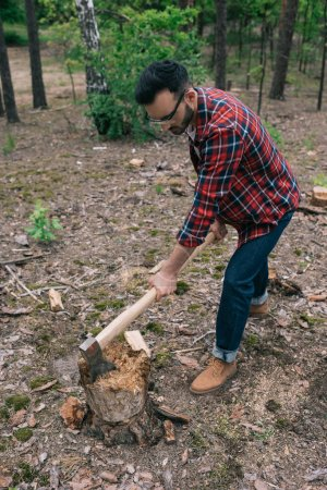 Photo for Lumberjack in plaid shirt and denim jeans cutting wood with ax in forest - Royalty Free Image