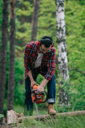 Photo pour Bûcheron dans les protecteurs auditifs coupe du bois avec tronçonneuse dans la forêt - image libre de droit