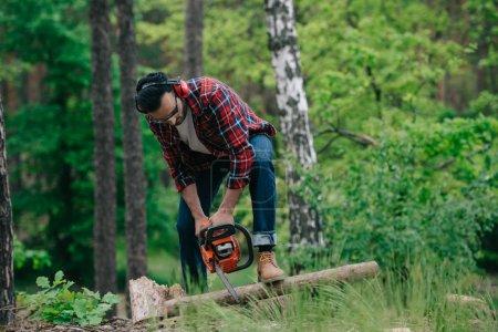 Photo pour Bûcheron en chemise à carreaux et jeans en denim coupant du bois avec tronçonneuse en forêt - image libre de droit