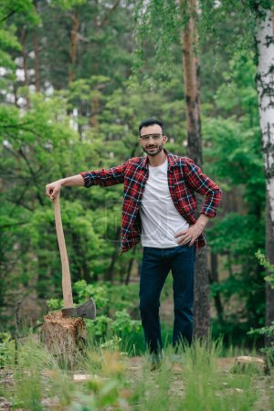 Photo for Cheerful lumberjack in plaid shirt and denim jeans holding ax while standing with hand on hip and smiling at camera - Royalty Free Image