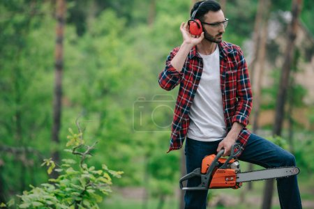 Foto de Lumberjack in plaid shirt standing with chainsaw in forest and touching noise-canceling headphones - Imagen libre de derechos