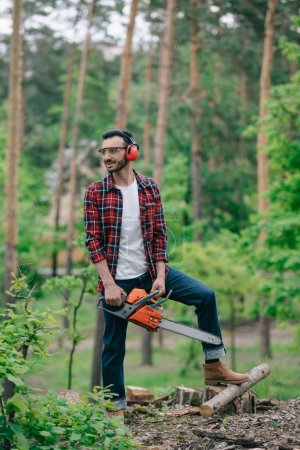 Photo for Smiling lumberman in plaid shirt and denim jeans standing with chainsaw in forest and looking away - Royalty Free Image