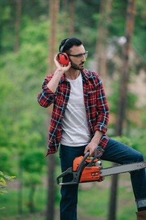 Photo pour Bûcheron sérieux en chemise à carreaux debout avec tronçonneuse en forêt et protecteurs auditifs touchants - image libre de droit