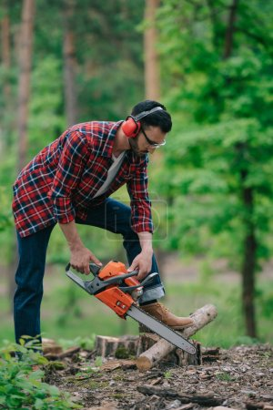 Photo for Lumberer in noise-canceling headphones cutting wood with chainsaw in forest - Royalty Free Image