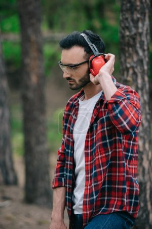 Photo for Pensive lumberjack in protective glasses standing in forest and touching noise-canceling headphones - Royalty Free Image