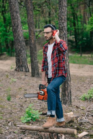Photo for Thoughtful lumberjack holding chainsaw, touching noise-canceling headphones and looking away - Royalty Free Image