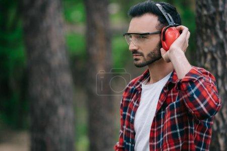 Photo pour Bûcheron pensif touchant des écouteurs antibruit et regardant loin dans la forêt - image libre de droit