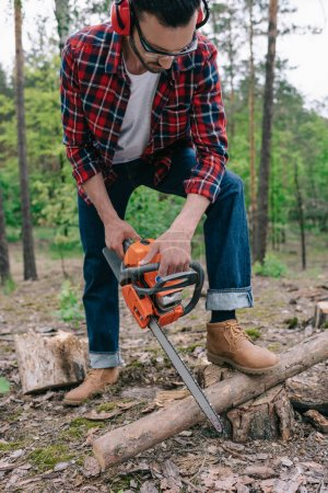 Photo for Lumberer in plaid shirt and denim jeans cutting wood with chainsaw in forest - Royalty Free Image