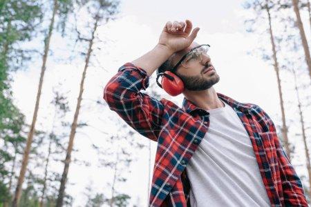 Photo pour Bûcheron fatigué dans des lunettes protectrices retenant la main près de la tête et regardant loin dans la forêt - image libre de droit