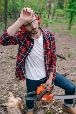 exhausted lumberjack with chainsaw holding hand near head and looking away in forest