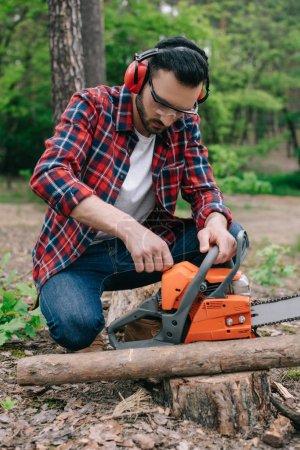Photo pour Bûcheron en chemise à carreaux et protecteurs auditifs ajustant la tronçonneuse dans la forêt - image libre de droit