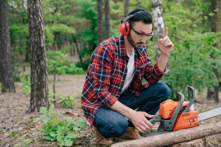 Photo for Lumberjack in noise-canceling headphones sitting in forest near chainsaw and showing idea gesture - Royalty Free Image