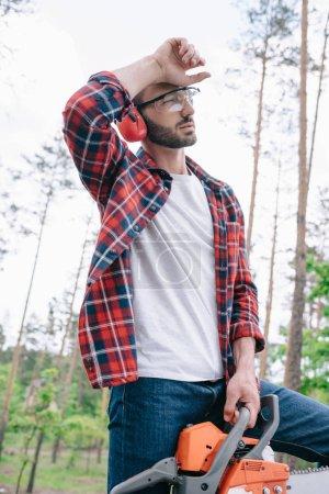 Photo pour Bûcheron fatigué dans des lunettes de protection et des cache-oreilles tenant la tronçonneuse et regardant loin dans la forêt - image libre de droit