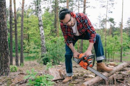 Photo pour Bûcheron en chemise à carreaux et jeans en denim coupe rondins avec tronçonneuse en forêt - image libre de droit