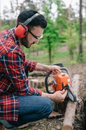 Photo for Lumberman in noise-canceling headphones fixing chainsaw in forest - Royalty Free Image
