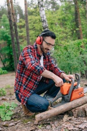 Photo pour Bûcheron dans les écouteurs antibruit ajustant la tronçonneuse dans la forêt - image libre de droit