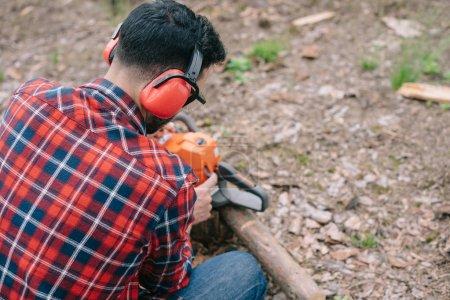 Photo pour Vue arrière du bûcheron dans les protecteurs auditifs réparation tronçonneuse dans la forêt - image libre de droit