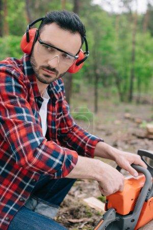 Photo pour Bûcheron sérieux dans les cache-oreilles et les protecteurs auditifs regardant loin dans la forêt - image libre de droit
