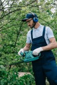 gardener in noise-canceling headphones pruning bushes with electric trimmer