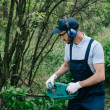 gardener in noise-canceling headphones and overalls pruning bushes with electric trimmer
